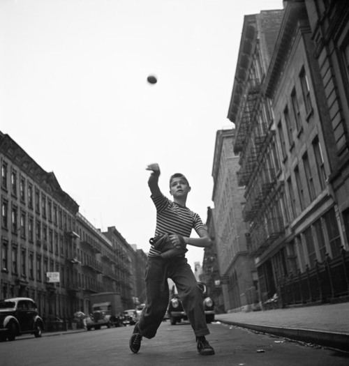 Young boy tossing a ball on a city street.